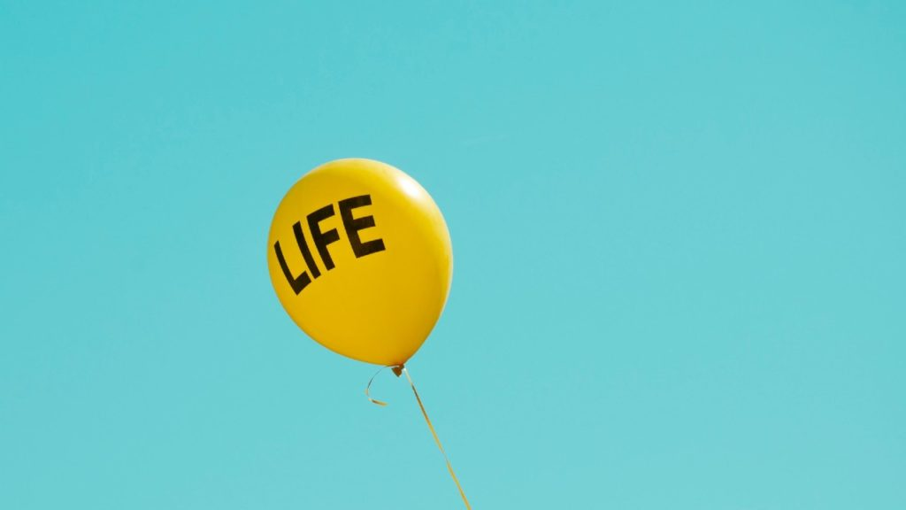 """yellow balloon with the word """"life"""" in black letters"""